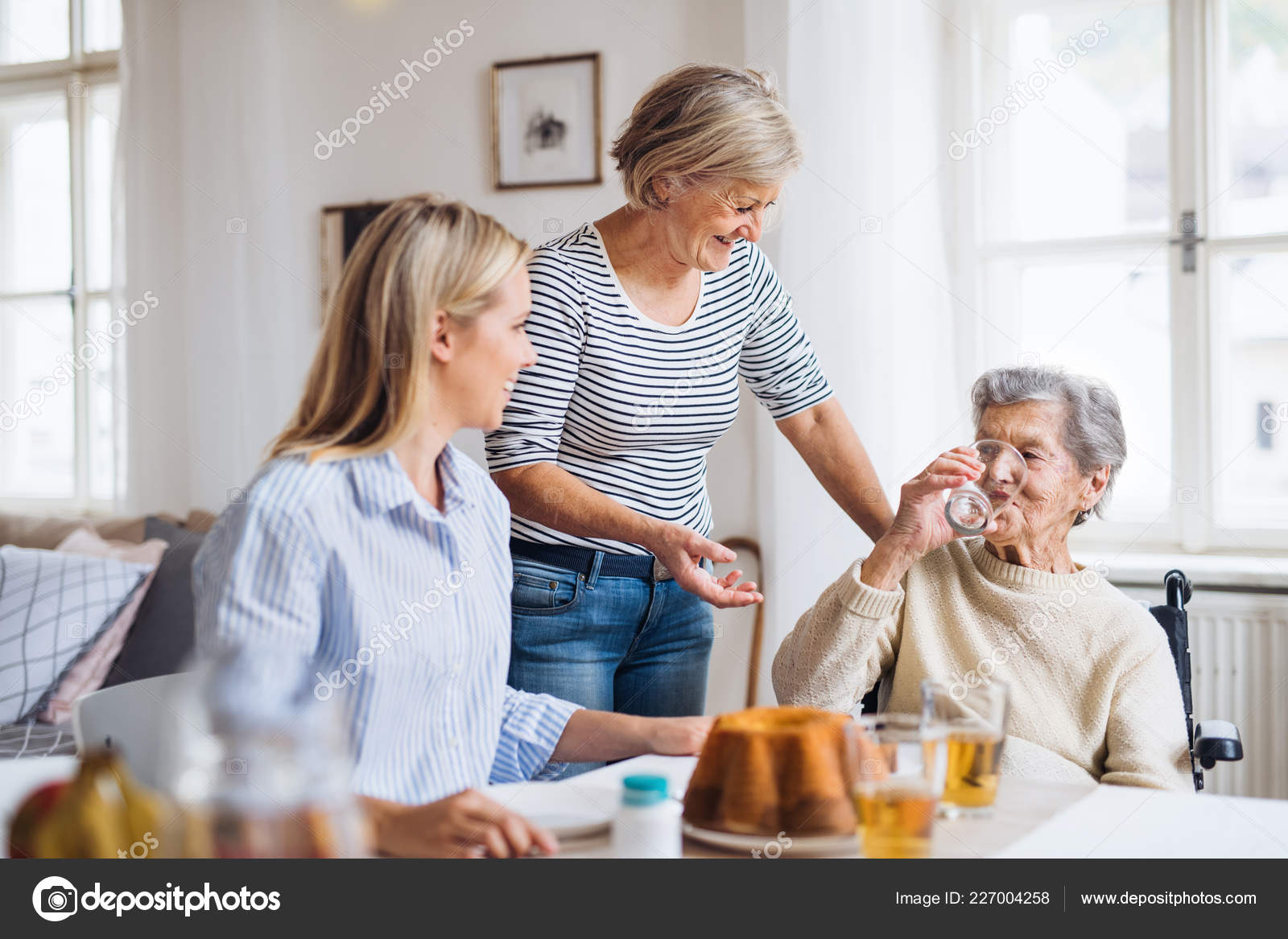 senior woman in wheelchair with family sitting at the table at home