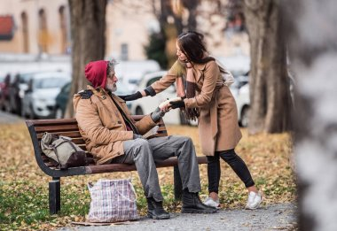 Young woman giving food to homeless beggar man sitting on a bench in city.