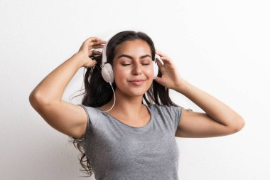 Young beautiful happy woman with headphones in studio, eyes closed.
