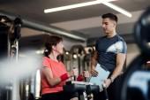 eine Seniorin mit einem jungen Trainer beim Krafttraining im Fitnessstudio.