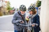 Aktives Seniorenpaar mit Elektrofahrrädern steht draußen auf Gehweg in der Stadt.