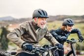 Aktives Seniorenpaar mit Elektrofahrrädern unterwegs in der Natur.