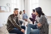 Hlavní poradce s schránky mluvit s mužem během skupinové terapie.