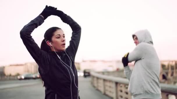 ein fittes Paar Läufer beim Stretching im Freien auf der Brücke in Prag.
