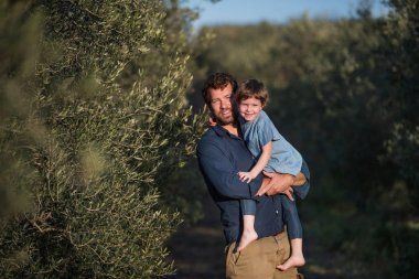 Father with small daughter standing outdoors by olive tree.