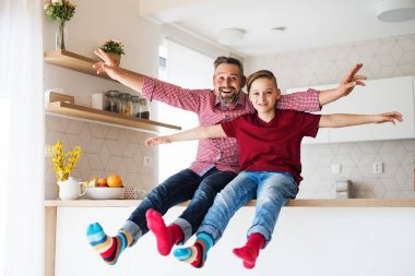 Mature father with small son sitting on kitchen counter indoors, having fun.