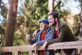 Fotografie Senior Vater und sein Sohn spazieren in der Natur, stehen und reden.