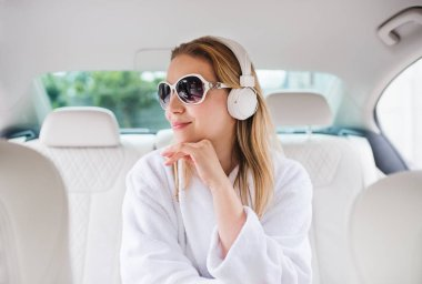 Young woman with sunglasses and headphones sitting in car in dressing gown.