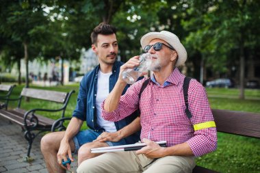 A young man and blind senior with white cane sitting on bench in park in city, drinking water. stock vector