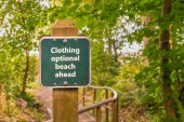 Photo Clothing optional sign on post on trail to beach, British Columb
