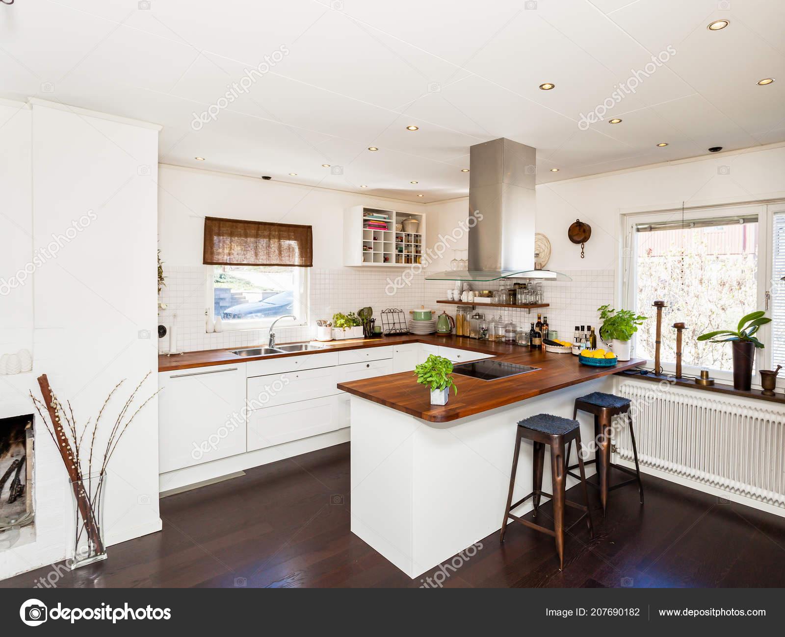 Elegante cucina con armadi bianchi con tavoli legno pavimento scuro