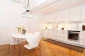 Fotografia interiore di una cucina bianca con tavolo da cucina