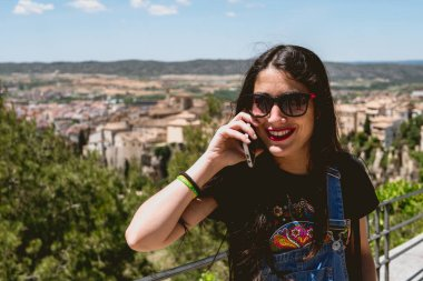 beautiful woman talking on the phone from a panoramic view of the charming city
