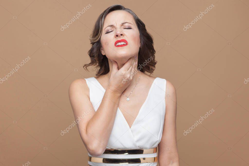 Mujer Vestido Blanco Tocar Garganta Sobre Fondo Marrón Claro