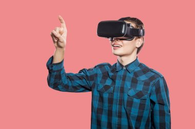 young man wearing checkered shirt with vr headset touching imaginary screen on pink background
