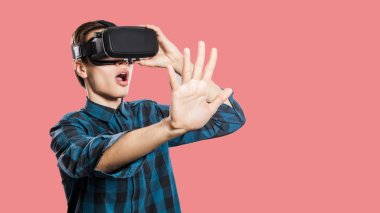 wondered young man with vr headset trying to touch imaginary reality on pink background