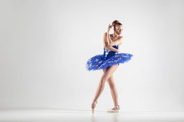 Young beautiful ballerina dancing gracefully isolated on white background
