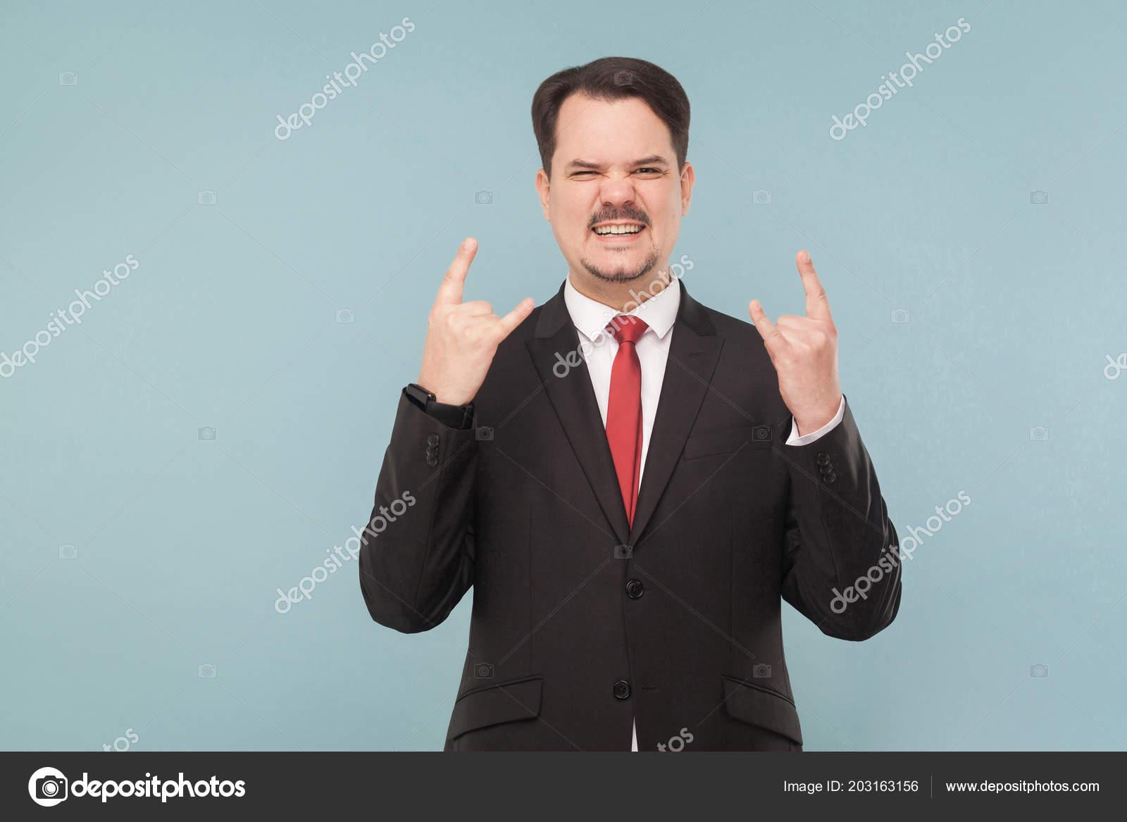 d55835492f0b Uomo d u0027affari con i baffi vestito nero e cravatta rossa mostrando rock  and roll segno sulla luce di sfondo blu canta  u2014 Foto di khosrork ...