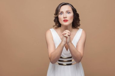 Unhappy worried woman in white dress holding hands in apologize gesture on brown background