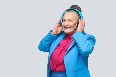 Trendy happy grandmother in colorful casual style holding blue headphones while listening to music on gray background