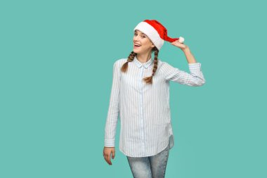 happy funny beautiful woman in striped blue shirt standing and touching red christmas hat while looking at camera with toothy smile on green background, New year concept