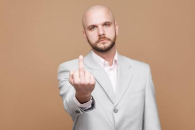 Portrait of serious middle aged bald bearded businessman in light gray suit looking at camera and showing middle finger with poker face on brown background