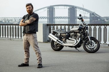 Redhead biker with beard in leather jacket standing with crossed arms near motorbike on bridge