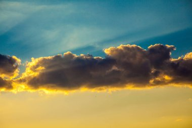 fluffy grey clouds illuminated by yellow sunrise in sky