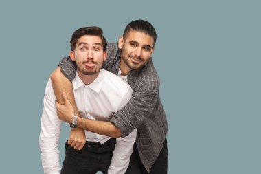 portrait of two handsome happy bearded friends enjoying and hugging while looking at camera with smile and funny face on blue background
