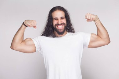 Portrait of strong bodybuilder man in white t-shirt with long wavy hair and beard posing with raised arms and showing biceps with muscular body on gray background