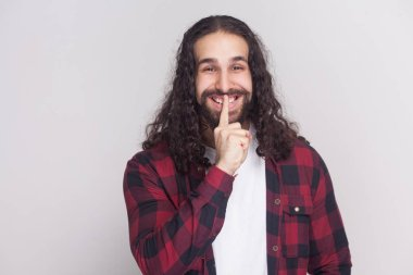 funny man with beard and black long curly hair in checkered red shirt standing and showing silent sign for secret on grey background