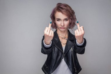 Portrait of aggressive woman with short pink hairstyle and makeup in black leather jacket standing and looking at camera while showing middle fingers