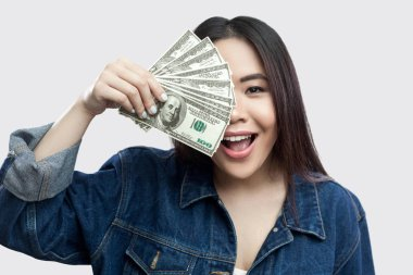 Portrait of beautiful happy young asian woman in blue denim jacket holding cash dollars and covering half of face with toothy smile on gray background stock vector