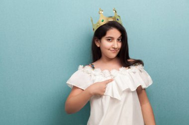 arrogance beautiful brunette girl wear in white dress and golden diadem crown standing and pointing finger to herself on blue background
