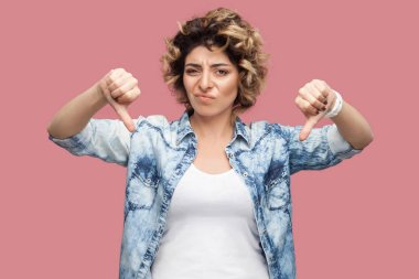 sad young woman with curly hairstyle in casual blue shirt showing thumbs down and looking at camera with dissatisfied face on pink background