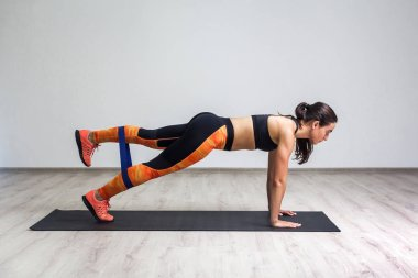Side view of strong athletic young caucasian woman in sportswear lying on mat and training legs and glutes muscle while using fitness elastic band in gym