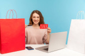 Happy woman buyer surrounded by packages smiling and holding credit card with Sale inscription, making purchases online on laptop using shopping loan. indoor studio shot isolated on blue background
