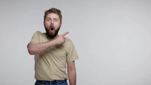 Surprised bearded guy in t-shirt pointing aside and looking with open mouth amazed shocked extremely excited, showing blank copy space for unbelievable advertise. studio shot isolated, gray background