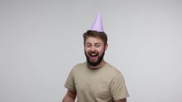 Úžasný šťastný nadšený vousatý muž s legračním mejdanovým kloboukem ukazujícím zabalenou dárkovou krabici a smějící se, vzrušený z dárků, oslavující narozeninové výročí. studio záběr izolované na šedém pozadí