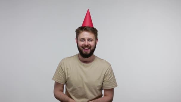 Optimistický radostný vousatý chlapík s legračním kuželovým kloboukem, který se směje a fouká konfety, oslavuje narozeniny gratulací k výročí, slavnostní náladě. studio záběr izolované na šedém pozadí