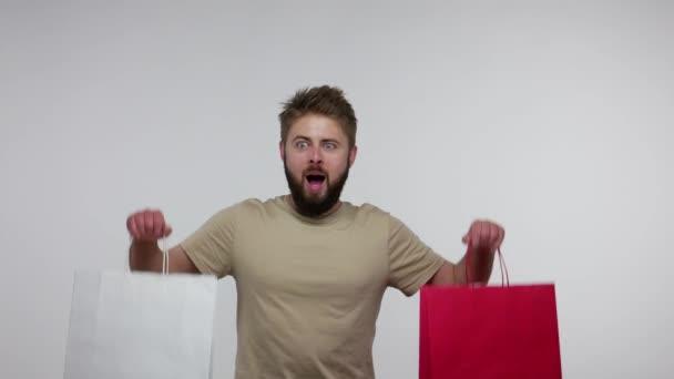 Vzrušené šťastné emoce klienta obchodu, usměvavý vousáč v tričku zvedající nákupní tašky, vypadá spokojeně s nákupem, prodejem a slevou. vnitřní studio záběr izolované na šedém pozadí