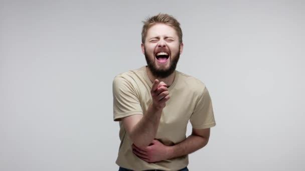 K popukání. Radostný vousáč ukazující prstem na kameru, hlasitě se smál, dělal si legraci ze směšného vzhledu, pobavený vtipem. vnitřní studio záběr izolované na šedém pozadí