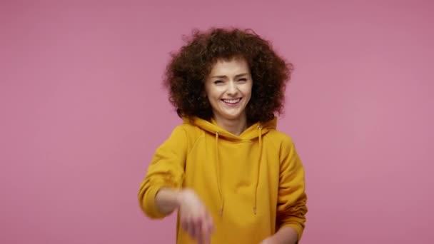 Hej ty! Pobavená dívka afro účes v mikině ukazuje prstem na kameru, hlasitě se směje, posmívá se směšné vzhled, legrační vtip. vnitřní studio záběr izolované na růžovém pozadí