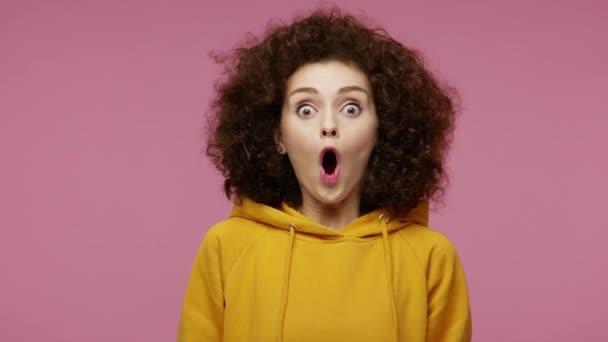 Nemůžu tomu uvěřit! Překvapená dívka afro účes v mikině při pohledu do kamery s velkýma očima překvapený výraz, otevřená ústa v úžasu. studio záběr izolované na růžovém pozadí