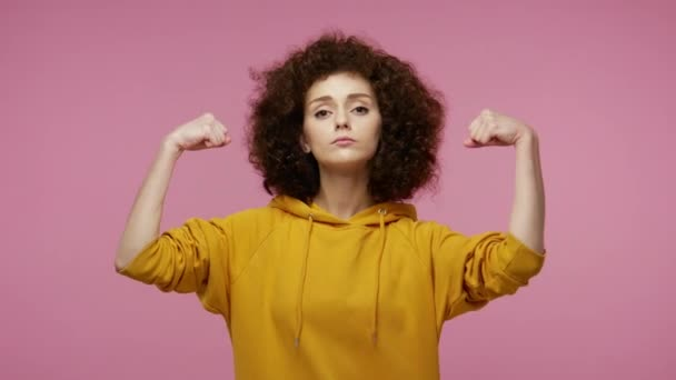 I am strong and independent! Girl afro hairstyle in hoodie showing biceps and looking confident, feeling power strength to fight for female rights. indoor studio shot isolated on pink background