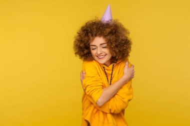 Portrait of selfish curly-haired hipster girl with funny cone hat embracing herself and smiling with pleasure expression, self-loving and complacency concept. studio shot isolated on yellow background