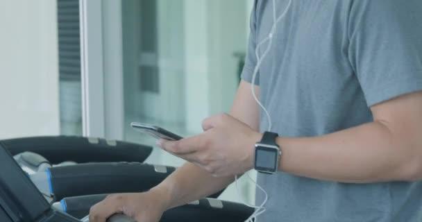 Junge asiatische Mann laufen auf dem Laufband im Fitnessstudio mit Kopfhörer.