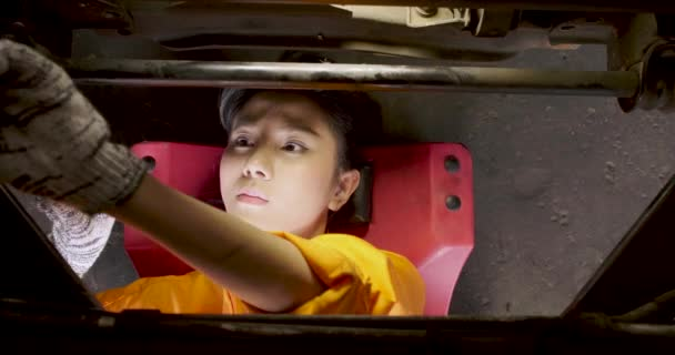 Young beautiful car mechanic is lying under the car to repairing it.
