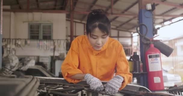 Young beautiful car mechanic repairing a car in a garage.