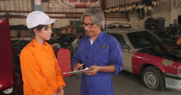 Mechanics discussing over clipboard in a car workshop.
